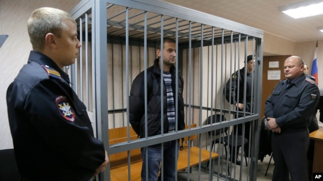 A police officers guards a cage with Greenpeace activist  Ruslan Yakushev of Ukraine in a courtroom in Murmansk, Russia, Sept. 26, 2013.