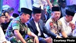 Presiden Joko Widodo (tengah) didampingi Panglima TNI Marsekal Hadi Tjahjanto (kiri) dan Kapolri Jenderal Tito Karnavian (kanan) dalam acara buka puasa bersama di di Lapangan Monumen Nasional, Jakarta, Kamis, 16 Mei 2019.