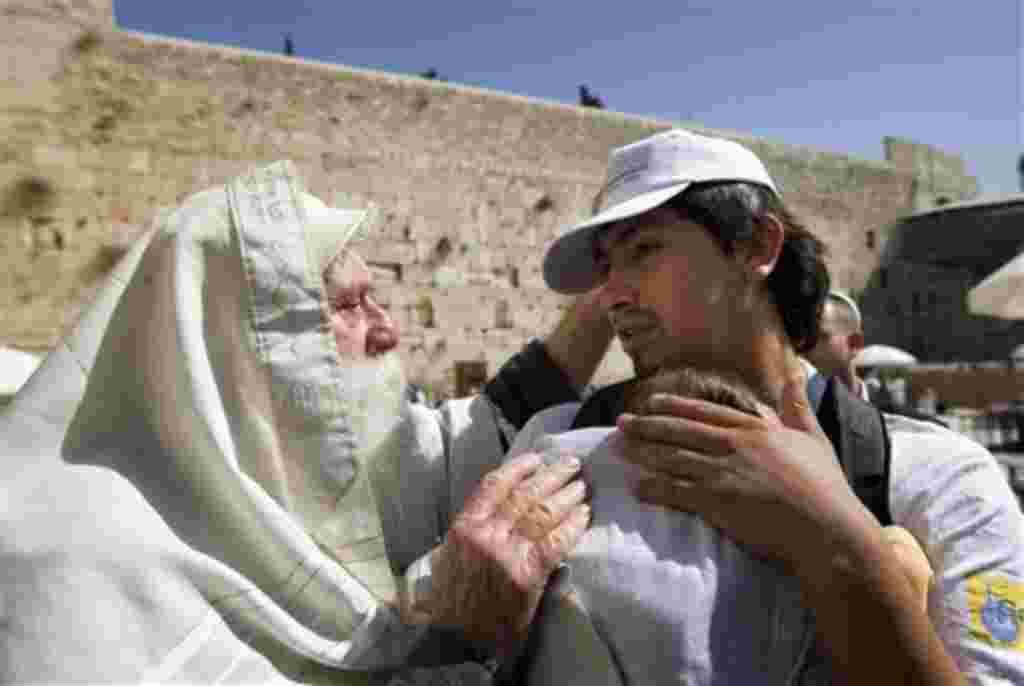 Uno de los mineros chilenos y su hijo es bendecido por un judío durante su visita a la ciudad de Jerusalén.