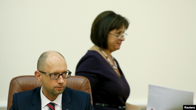 FILE - Ukrainian Finance Minister Natalia Yaresko (R) walks past Prime Minister Arseny Yatseniuk during a government meeting in Kyiv.