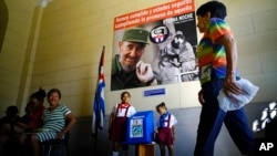 Back-dropped by a poster of the late Fidel Castro, a woman arrives at a polling station to cast her vote in municipal elections in Havana, Cuba, Nov. 26, 2017.