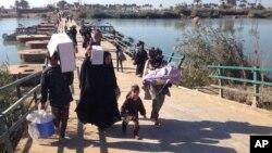 Ramadi'den kaçmaya çalışan Iraklı siviller, Bağdat yolunu yürüyerek takip etmek zorunda.
