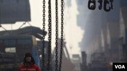 河北省唐山曹妃甸港的一名碼頭工人等待把鋼筋裝上貨輪。(2012年2月20日)