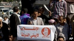 "A protester holds a banner with Arabic writing that reads, ""The coup does not build a country,"" protesting against Houthi Shiite rebels who hold the capital, Sanaa, amid a power vacuum as they hold a demonstration in Saturday, Jan. 24, 2015."