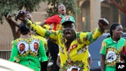 FILE:Supporters of Zimbabwean President Emmerson Mnangagwa celebrate in Harare, Friday, August, 24, 2018. Zimbabwe's constitutional court on Friday unanimously upheld Mnangagwa's narrow victory in the 2018 presidential election after the opposition alleged vote-rigging.