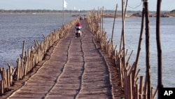 Cambodians ride across a Mekong bamboo bridge in Kom pong Cham, Cambodia Saturday, Dec. 20, 2014. The bridge is constructed every dry season for locals to travel over. The bridge is taken down before the wet session comes to prevent it being washed away. (AP Photo/Nick Ut)
