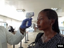 A passenger gets screened while departing Lungi airport, Freetown, Sierra Leone, Feb. 3, 2015. (Nina deVries/ VOA)
