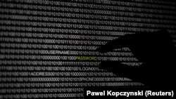 A hand is silhouetted in front of a computer screen in this picture illustration taken in Berlin May 21, 2013. The Financial Times' website and Twitter feeds were hacked May 17, 2013,