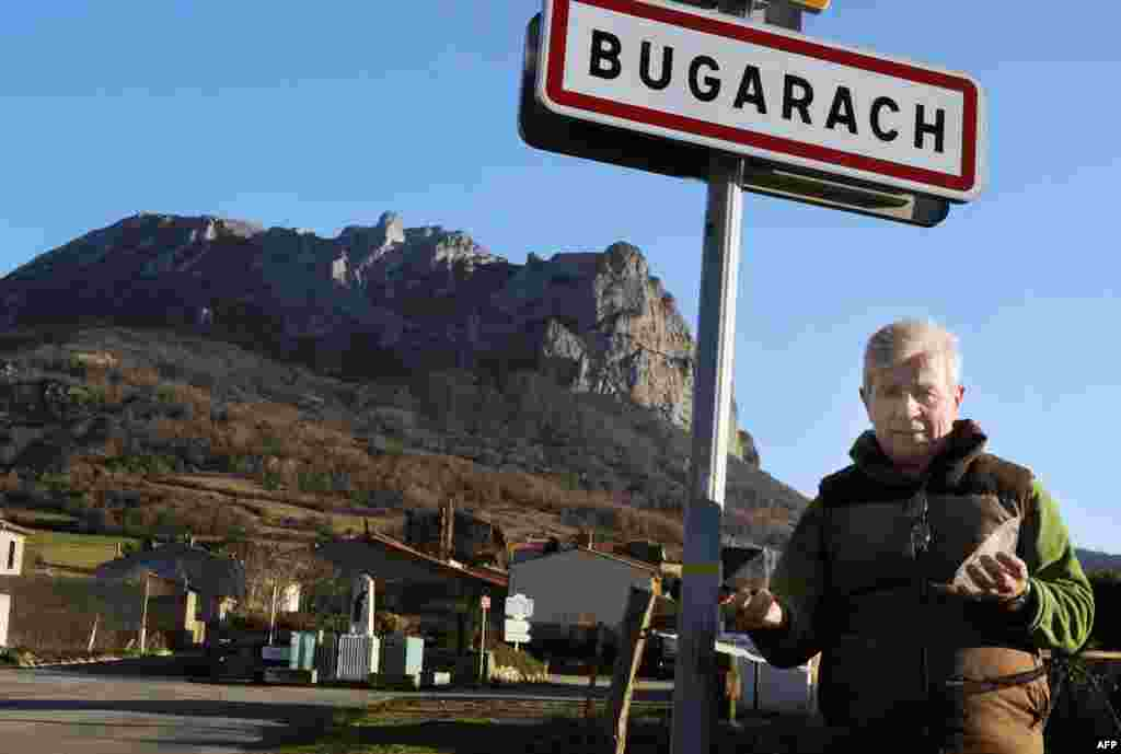 Bugarach Mayor Jean-Pierre Delord poses in front of a road sign, Dec. 14, 2010.