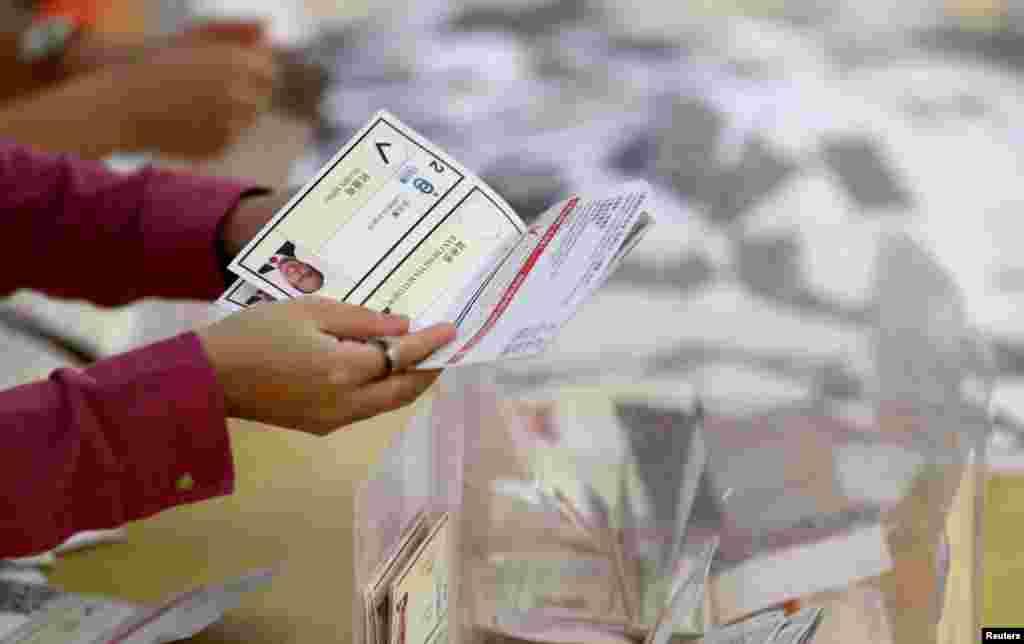 Una mujer sostiene una boleta electoral en un colegio electoral en Kowloon Tong, Hong Kong, China, 24 de noviembre de 2019.