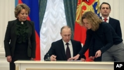 FILE - Russian President Vladimir Putin signs bills formalizing Russia's annexation of Ukraine's Crimean peninsula, in the Kremlin in Moscow, March 21, 2014.