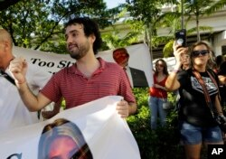 """FILE - Thomas Kennedy, 25, protests outside of a rally for Republican presidential nominee Donald Trump, in Miami, Sept. 16, 2016. """"One of the things that scares me the most is that this wretched man, Trump, wins,"""" said Kennedy. After becoming a naturalized this year, the 25-year-old immediately registered to vote."""