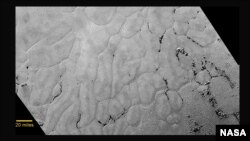 This July 14, 2015, photo provided by NASA shows an image taken from NASA's New Horizons spacecraft showing a new close-up image from the heart-shaped feature on the surface of Pluto that reveals a vast, craterless plain.