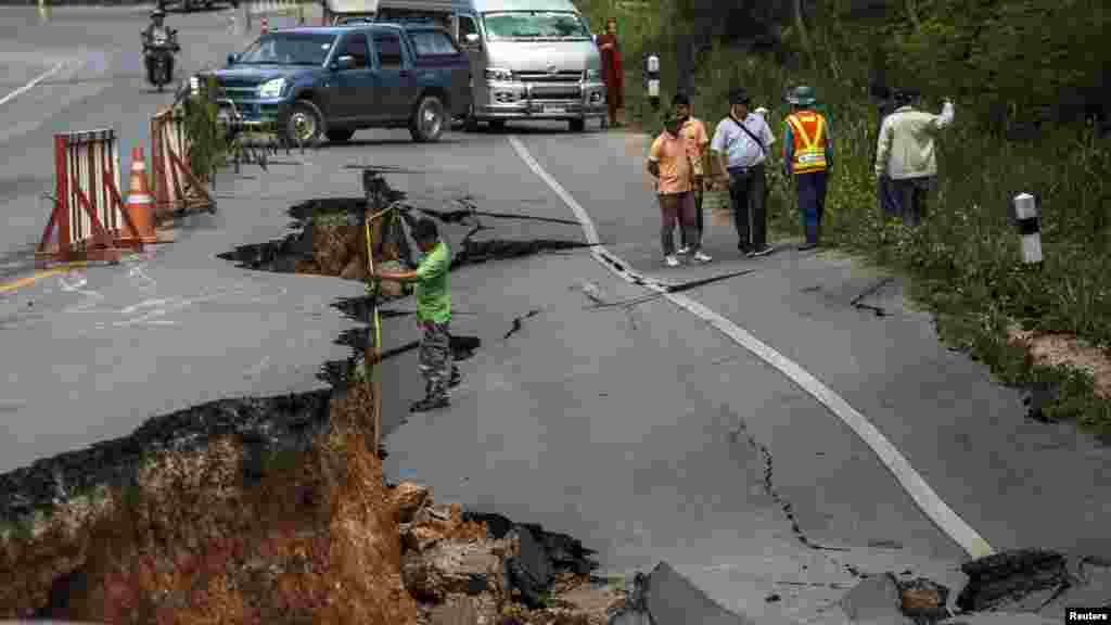 An officer measures the depth of a damaged section of highway which was caused by an earthquake May 5, 2014, in Chiang Rai, northern Thailand, May 6, 2014.