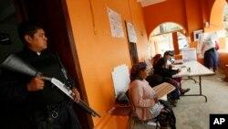 Un policía hace guardia en un colegio electoral en San Bartolomé Quialana, en las afueras de Oaxaca.