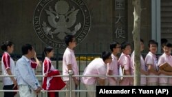 Chinese students wait outside the U.S. Embassy for their visa application interviews in Beijing, China.