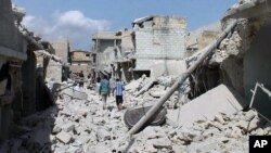 Warga Suriah berjalan di antara reruntuhan rumah-rumah yang rusak akibat serangan udara pemerintah Suriah di Aleppo, Suriah.