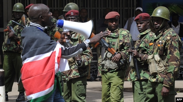 A supporter of presidential candidate Raila Odinga demonstrates as Kenyan policemen keep vigil outside the Supreme Court in Nairobi, Mar. 30, 2013.