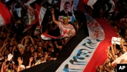 Supporters of Egypt's ousted President Mohammed Morsi hold a large Egyptian national flag as they chant slogans against Defense Minister Gen. Abdel-Fattah el-Sissi, in Cairo, Aug. 2, 2013.