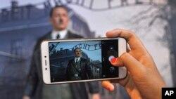 """Pengunjung menggunakan ponsel untuk mengambil foto lilin angka Adolf Hitler berlatar belakang kamp Auschwitz-Birkenau di Mata De Museum, Yogyakarta, Indonesia, 8 November 2017. (Foto: dok). Kelompok HAM mengecam menyebutnya """"memuakkan"""" dan menuntut tampilan ini agar segera disingkirkan."""