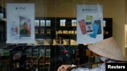Penjual buah berjalan melewati toko Apple di Hanoi (24 April 2014). Negara komunis Vietnam tiba-tiba menjadi pasar terhangat Apple setelah penjualan produk Apple meningkat tiga kali lipat dalam tiga bulan pertama tahun ini, jumlah yang lebih tinggi lima kali lipat daripada di India.