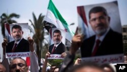 "Supporters hold posters of Egypt's Islamist President Mohammed Morsi during a rally near Cairo University Square in Giza, Egypt, Tuesday, July 2, 2013. Egypt was on edge Tuesday following a ""last-chance"" ultimatum the military issued to Mohammed Morsi, gi"