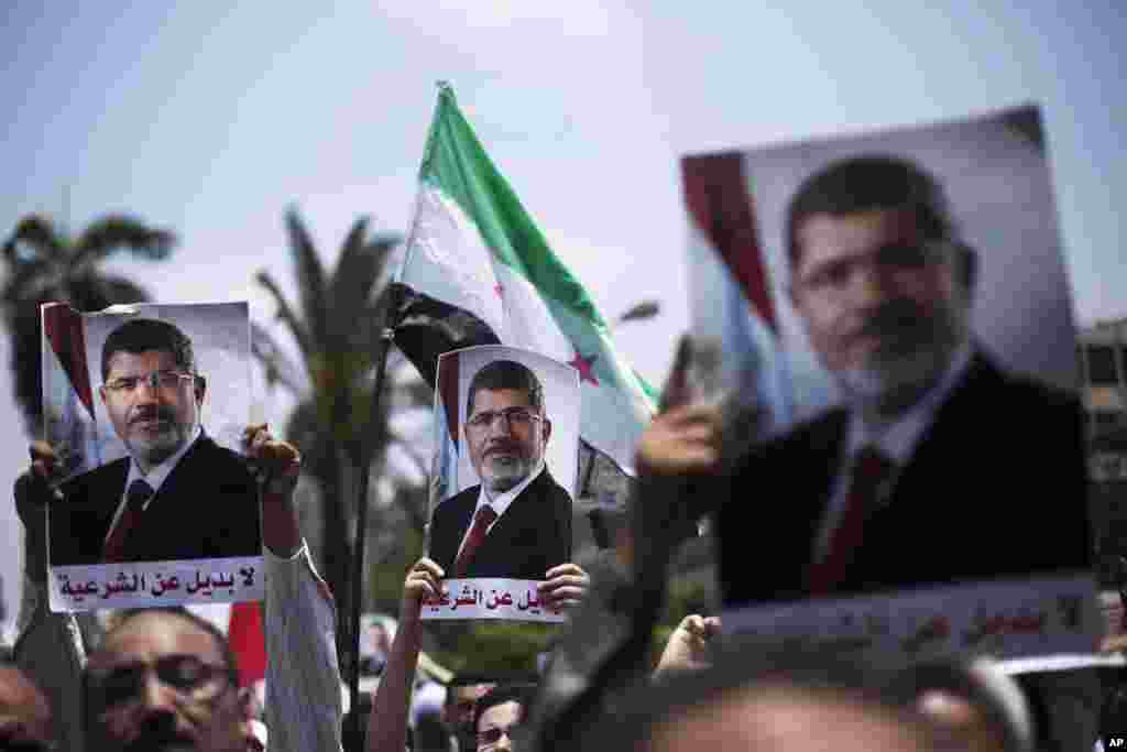 Supporters hold posters of Egypt's Islamist President Mohamed Morsi during a rally near Cairo University Square in Giza, July 2, 2013.