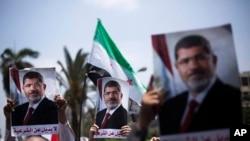2013年7月2日在开罗大学附近支持埃及总统穆尔西的群众高举拥护穆尔西的图片。