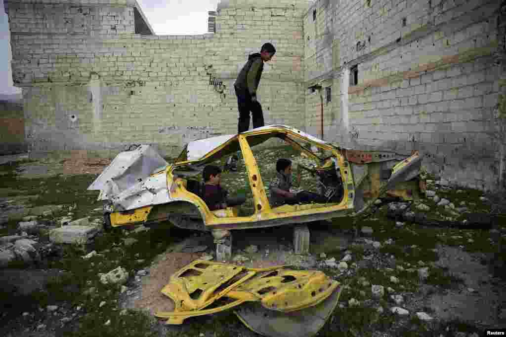 Anak-anak Suriah bermain dengan sebuah mobil rongsok di distrik Douma, Damaskus.