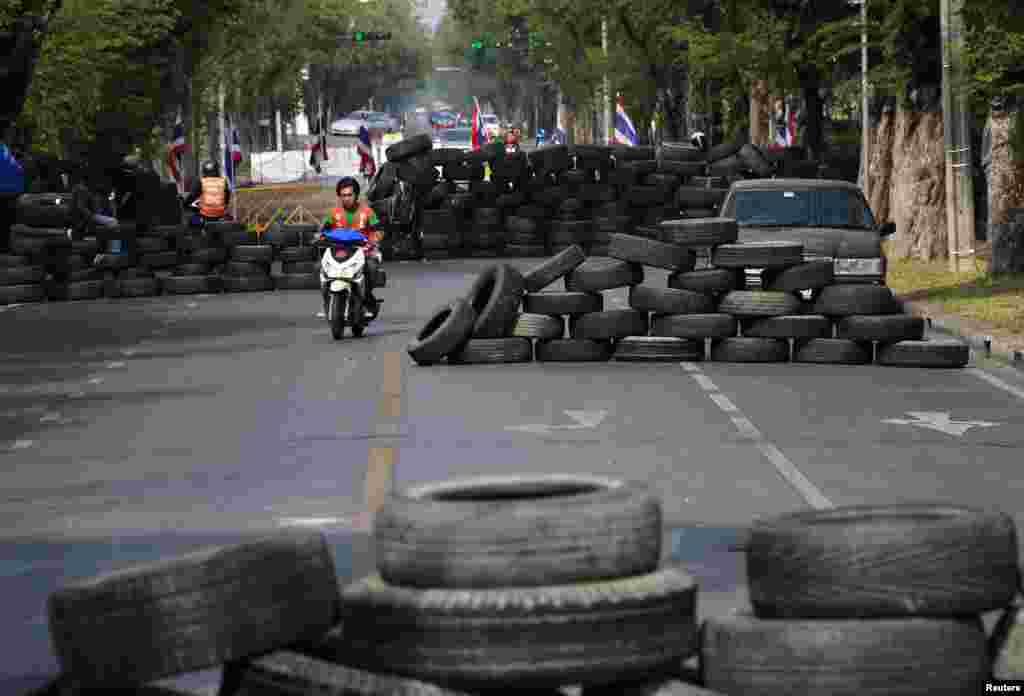 A motorcyclist rides past barricades constructed by anti-government protesters during a rally outside the Government House in Bangkok, Thailand, Dec. 29, 2013.