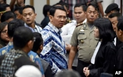 "Jakarta Governor Basuki ""Ahok"" Tjahaja Purnama, center, talks to his lawyers after his sentencing hearing at a court in Jakarta, Indonesia, Tuesday, May 9, 2017."