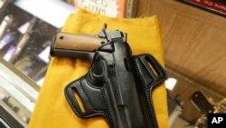 Una pistola semiautomática y un porta-pistolas se exhiben en una tienda de armas de Little Rock, Arkansas. Foto de Archivo.