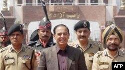 Bộ trưởng Nội vụ Pakistan Qamar-uz-Zaman Chaudhry đi cùng các sĩ quan an ninh biên giới Ấn Độ khi ông đến biên giới tại Wagah, Ấn Độ, Chủ Nhật 27/3/2011