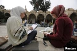 Youths read and draw in the Ottoman-era Tekkiye Suleimaniye mosque complex in Damascus, Syria, March 2, 2016.