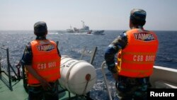 FILE: Vietnamese Marine Guard officers monitor a Chinese coast guard vessel (top) on the South China Sea, about 210 km (130 miles) offshore of Vietnam, May 15, 2014.