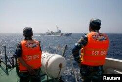 越南海岸警卫队成员在离越南海岸大约210公里处的南中国海海域观察一艘中国海警船。(2014年5月15日)