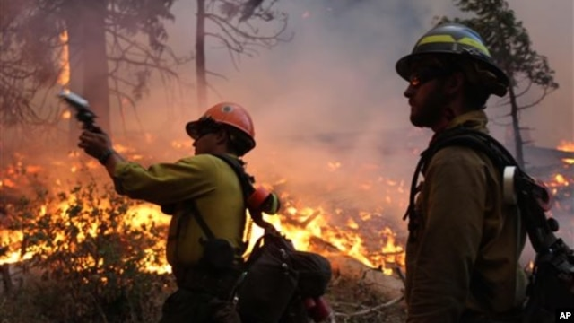 Fire crew members stand watch near a controlled burn operation as they fight the Rim Fire near Yosemite National Park in California, Sept. 2, 2013.