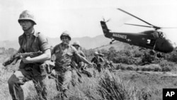 FILE - In this April 28, 1965 file photo, U.S. Marine infantry stream into a suspected Viet Cong village near Da Nang in Vietnam during the Vietnamese war. Filmmaker Ken Burns said he hopes his 10-part documentary about the War, which begins Sept. 17, 2017 on PBS, could serve as sort of a vaccine against some problems that took root during the conflict, such as a lack of civil discourse in America.