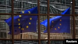 FILE - A European flag reflects in a building of the EU headquarters in Brussels.