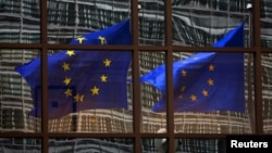 FILE - A European Union flag is reflected in a building of the EU headquarters in Brussels.