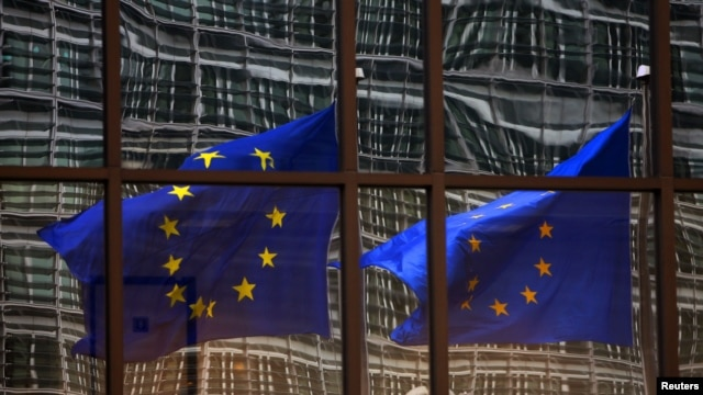 A European Union flag reflects on a building of EU headquarters in Brussels. The EU announced on Thursday, July 10, 2014 that it is imposing sanctions on South Sudanese officials who it says have been obstructing peace.