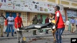 Equipas médicas removem um cadáver no local da explosão em Mogadíscio, Somália. 25 de Março, 2018