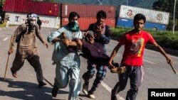 Pendukung Tahir ul-Qadri, ulama Sufi dan pemimpin partai politik Pakistan Awami Tehreek (PAT), membawa seorang demonstran yang cedera dalam Revolution March di Islamabad 31 Agustus 2014.