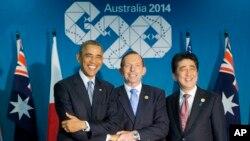 El presidente Barack Obama, y los primeros ministros, Tony Abbott, de Australia, y Shinzo Abe, de Japón, se entrelazan al inicio de su reunión tripartita en Brisbane, Australia.