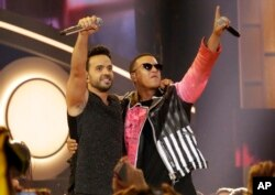 FILE - This April 27, 2017, photo shows singers Luis Fonsi, left, and Daddy Yankee during the Latin Billboard Awards in Coral Gables, Florida.