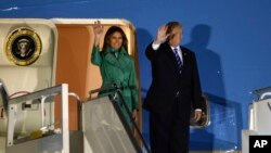 El presidente de EE.UU. Donald Trump y la primera dama Melania Trump, saludan desde su avión Air Force One a su llegada a Varsovia, la capital de Polonia, para una escala corta de camino a la Cumbre del G-20 en Alemania.