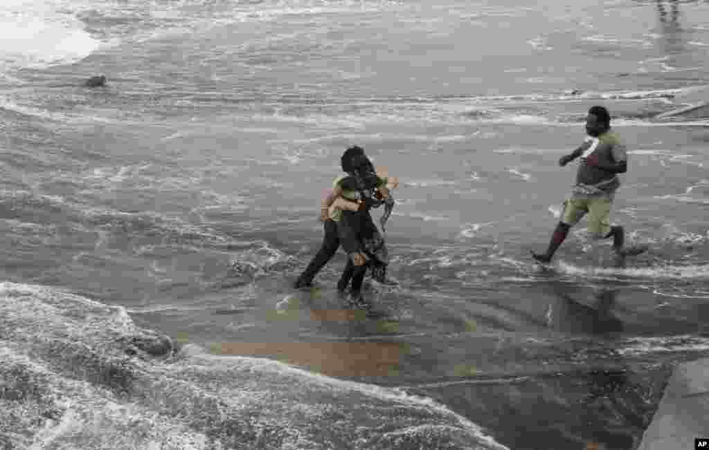 A man, right, rushes to help as another rescues a woman who fell due to strong tidal waves on the Bay of Bengal coast at Gopalpur, Orissa, Oct. 12, 2014.