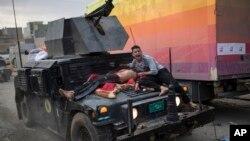 Seorang pria yang mengalami luka-luka diangkut dengan kendaraan pasukan khusus Irak dalam pertempuran di Mosul barat, Selasa (14/3).