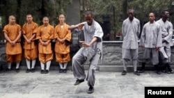 An African student (C) practices moves as other Shaolin martial arts students look on during the inauguration ceremony of a martial arts training program for African students, at the Shaolin Temple in Dengfeng, Henan province, China, Sept. 25, 2013.