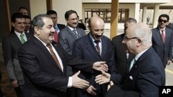 Iraqi Foreign Minister Hoshyar Zebari, left, welcomes Algeria's Foreign Minister Mourad Medelci, right, in Baghdad, Iraq, March 27, 2012.